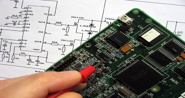 A green and black PCB with someone testing it with a probe sitting on a schematic.